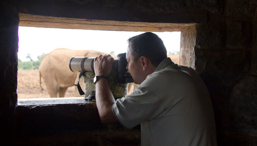 Mike taking pictures of elephant through opening in the elephant hide.